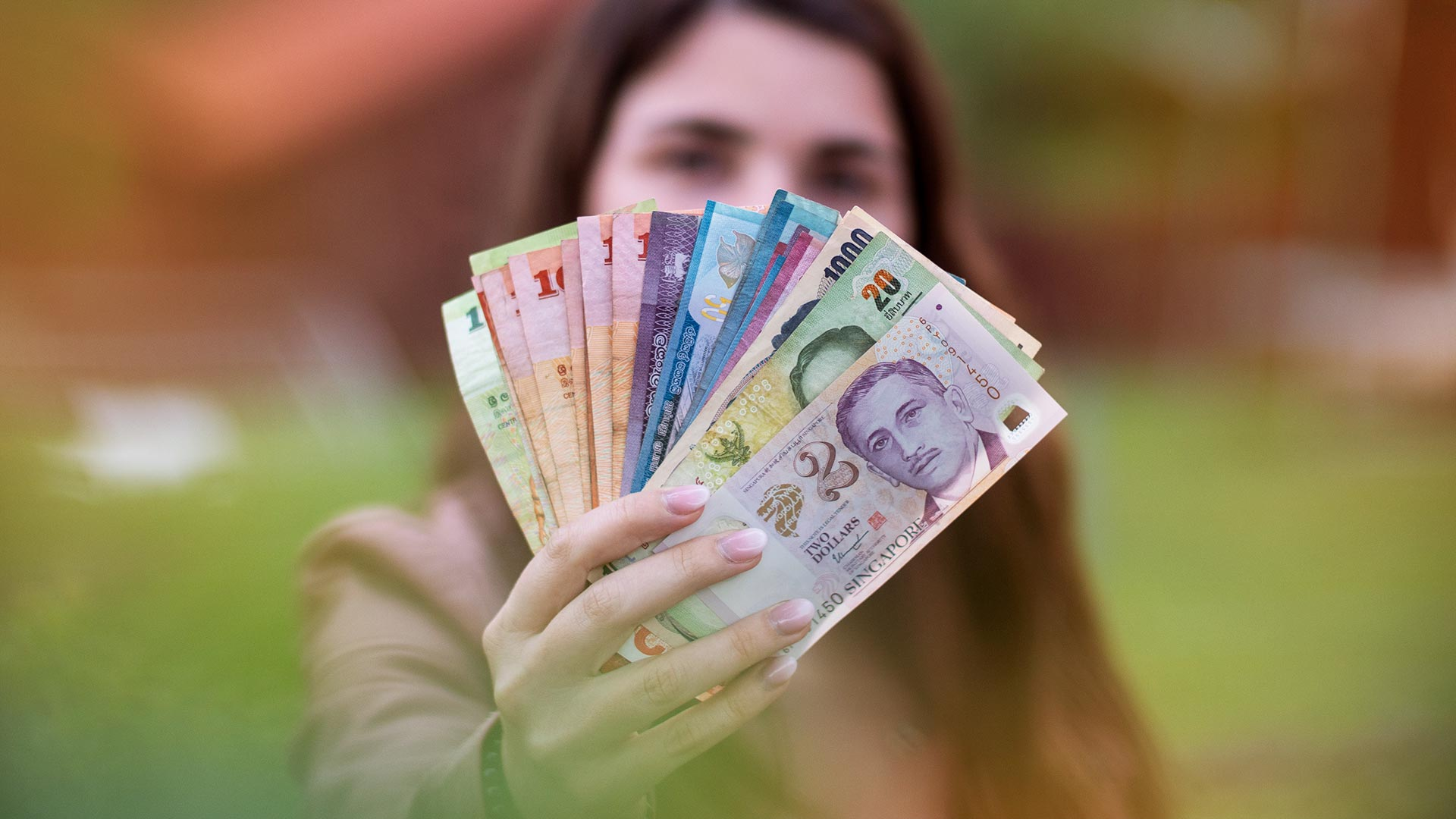Südostasien Backpacking Reisekosten - Jasmin mit Geldscheinen aus aller Welt