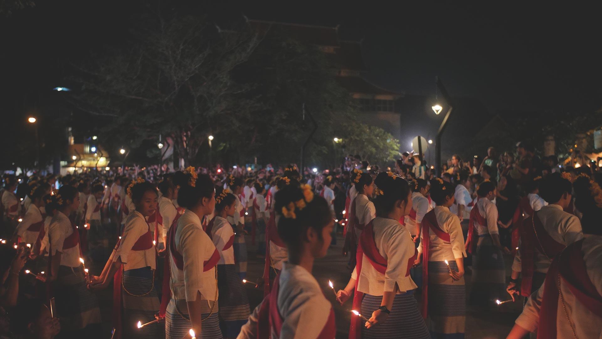 Loy Krathong Festival - Traditionell gekleidete Thailänderinnen in einer Zeremonie mit Kerzen