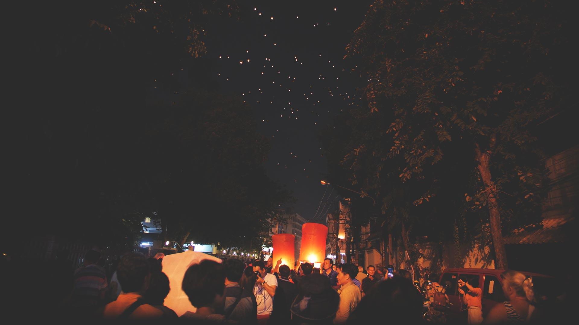Yee Peng Festival in Chiang Mai - Seitenstraße mit aufsteigenden Laternen am Horizont
