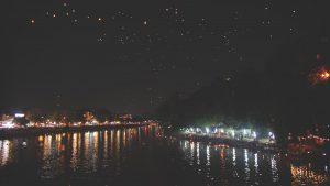 Loy Krathong und Yee Peng Festival in Chiang Mai - Aussicht von der Nawarat Bridge auf aufsteigende Laternen im Himmel und Schiffchen auf dem Fluss