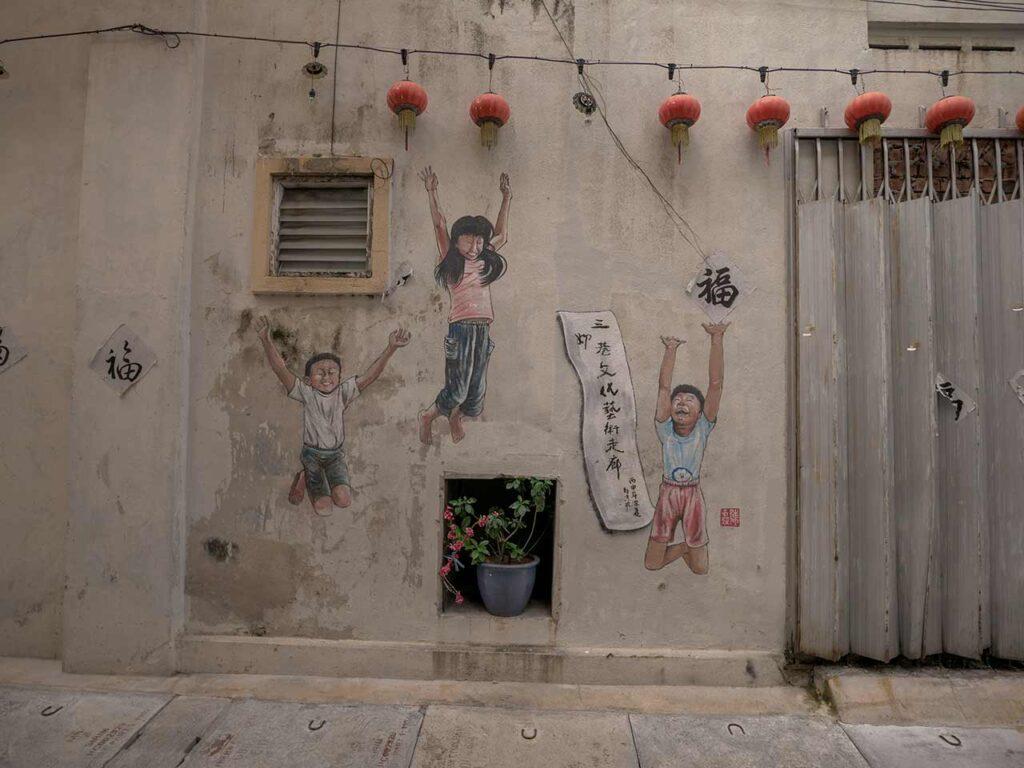 Streetart in der Market Lane: Drei Kinder springen nach oben