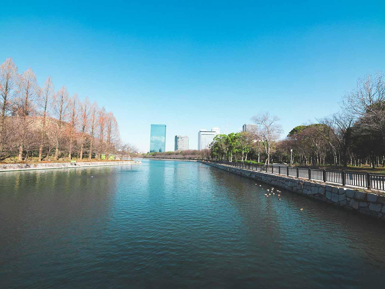 Fluss im Osaka Castle Park mit Hochhäusern im Hintergrund