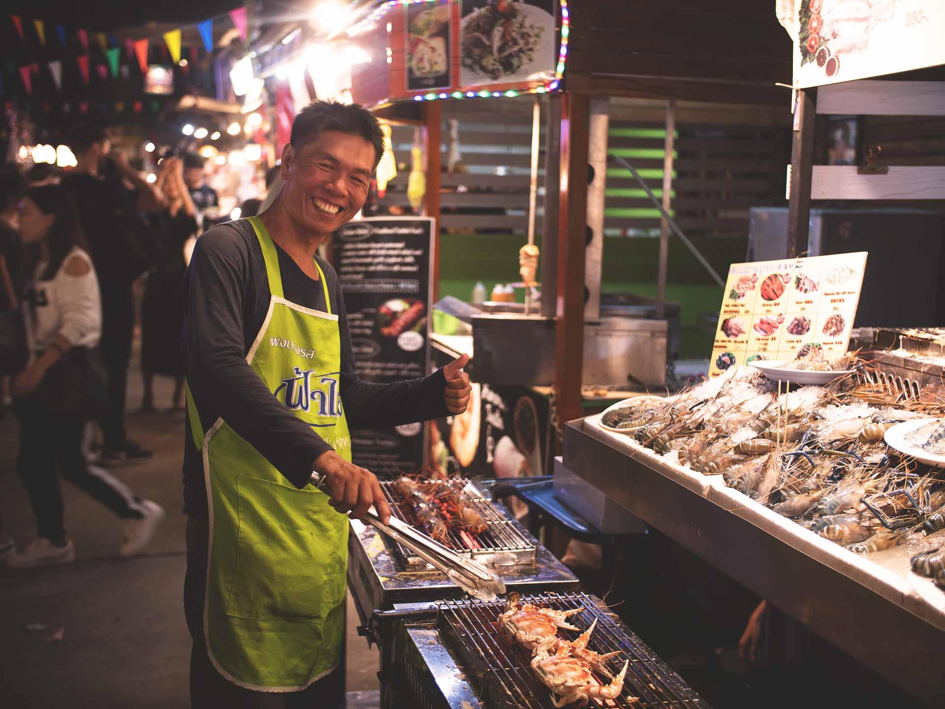 Thailänder mit großem Lächeln an einem Essensstand am Nachtmarkt in Chiang Mai