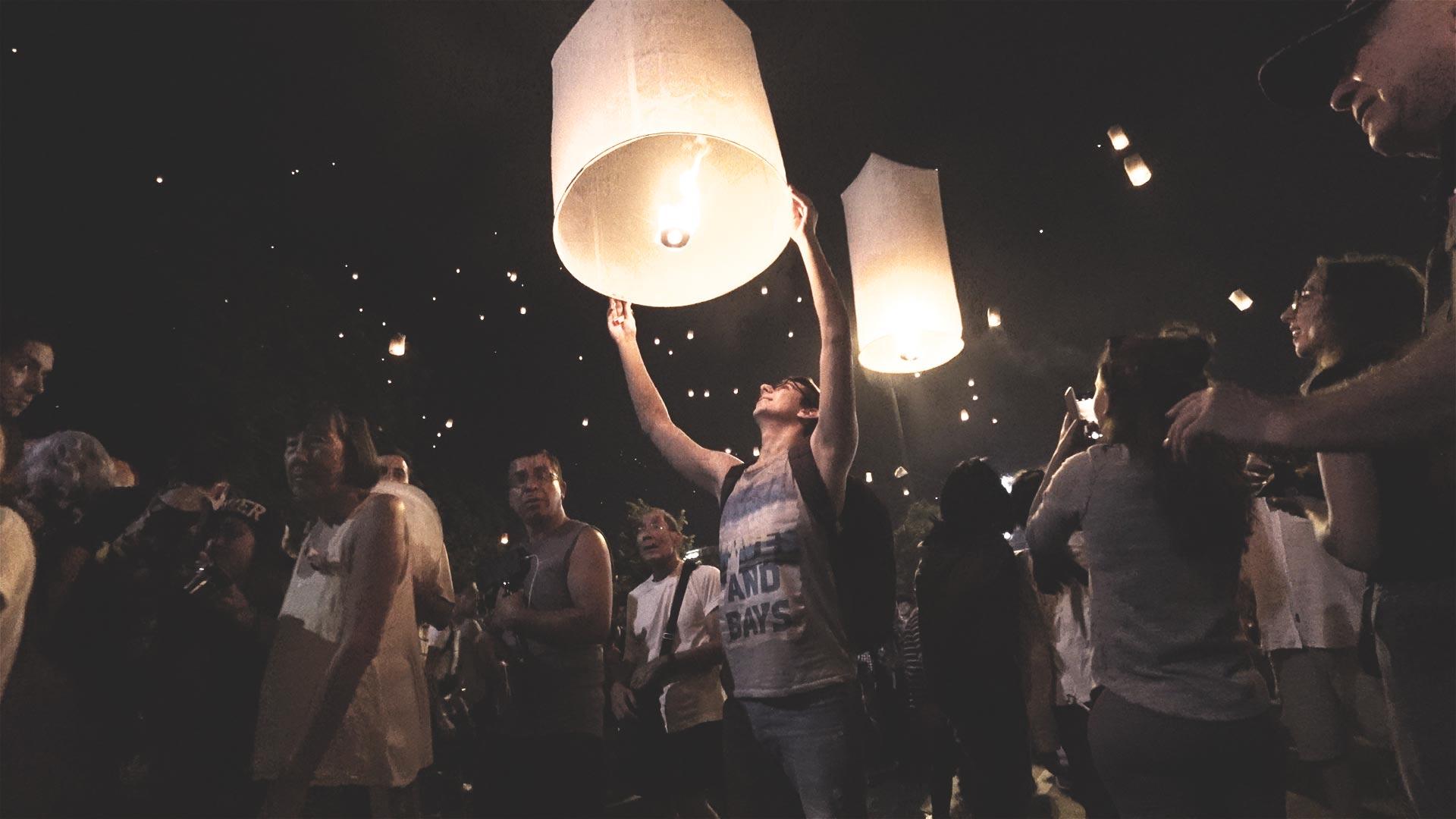 Yee Peng Festival in Chiang Mai - Valentin mit einer Laterne kurz vor dem Aufstieg